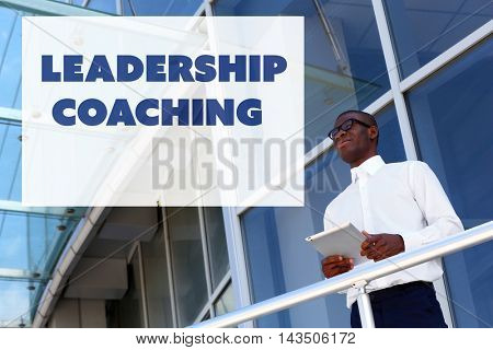 Leadership coaching concept. Handsome African American businessman with digital tablet near business centre