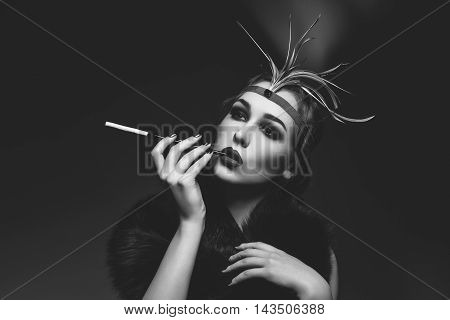 Beautiful young woman with smoky eyes and full red lips holding cigarette holder. Vintage head piece. Retro styling. Studio beauty shot. Copy space. Monochrome.