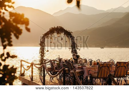Destination Wedding Arch And Banqouet Covered Table At Sunset