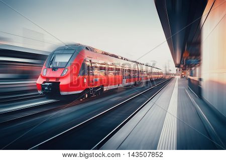Beautiful Railway Station With Modern Red Commuter Train In Motion