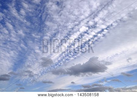 Fan of gray and white clouds on blue summer sky