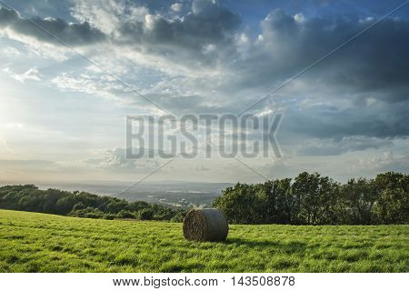 Beautiful Summer Vibrant Sunset Over Countryside Landscape Of Field With Hay Bales