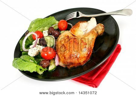 Meal of roast chicken and greek salad, on a black plate with fork and red napkin.  Isolated on white.