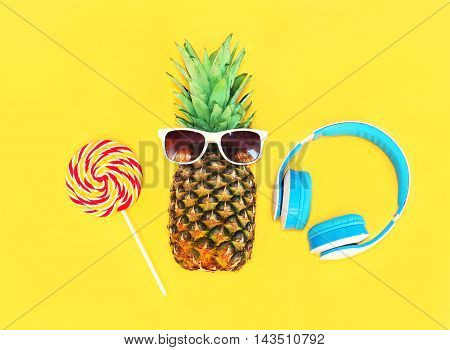 Fashion Pineapple With Sunglasses Lollipop Caramel And Headphones Over Colorful Yellow Background