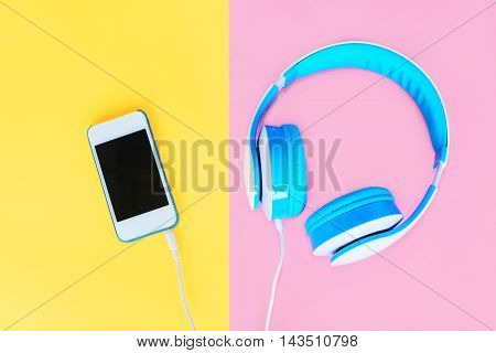 Headphones Connected To White Smartphone Over Colorful Yellow Pink Background