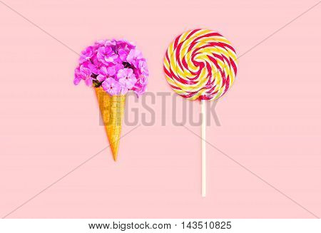 Ice Cream Cone Flowers And Colorful Lollipop Caramel On Stick Over Pink Background Top View