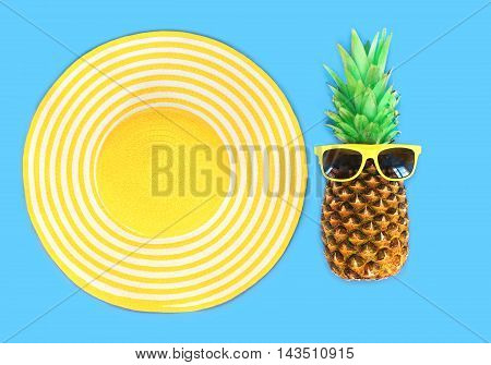 Pineapple With Sunglasses And Yellow Straw Beach Hat On Blue Background Top View