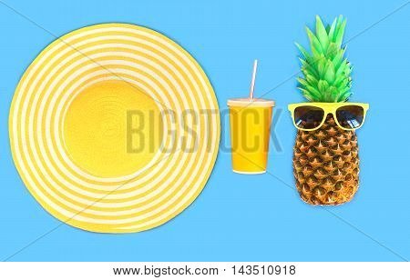 Pineapple With Sunglasses And Yellow Straw Beach Hat Cup Juice On Blue Background Top View