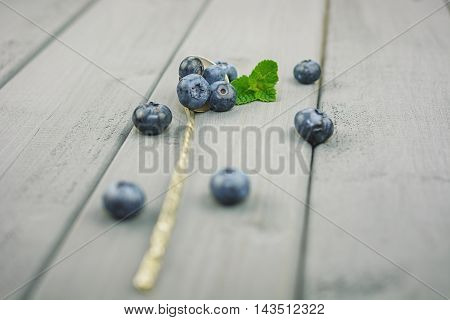 Spoon on a table filled with blueberries.