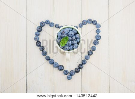 Blueberries are laid out on the table in the form of heart in a cup full of berries.