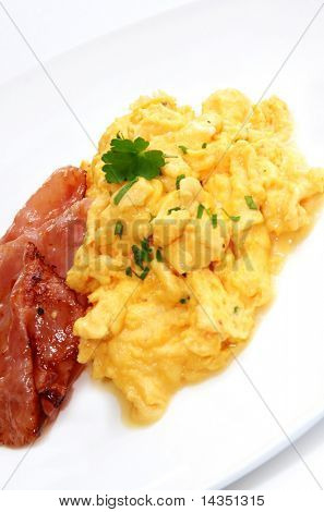 Breakfast of creamy scrambled eggs and bacon.