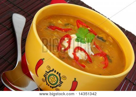 A yellow bowl of vegetarian chili, with red napkin and bamboo placemat.