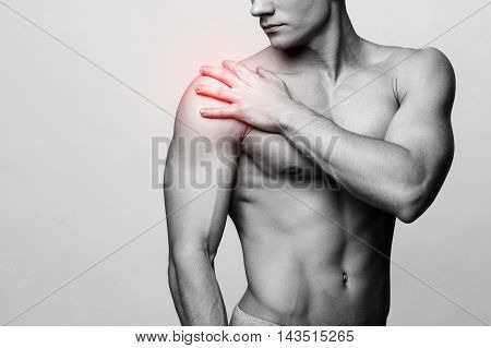 Studio shot of a young muscular man with pain problems