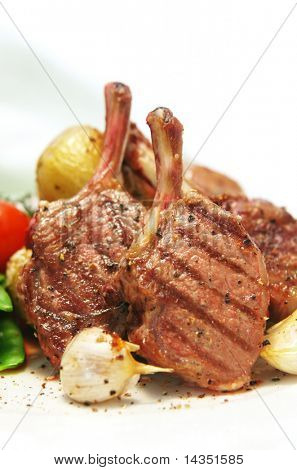 Lamb cutlets with roasted potatoes and garlic.  Closeup view.