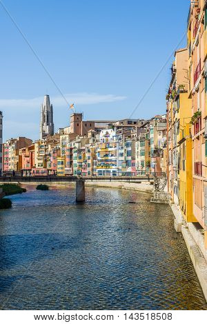 Onyar river crossing the downtown of Girona with bell tower of Basilica of Sant Feliu in background. Gerona Costa Brava Catalonia Spain.