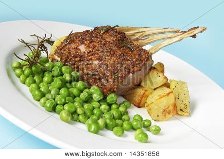 Rack of lamb with fresh-shelled peas and roasted potatoes.  The lamb is cooked with seeded mustard and rosemary.