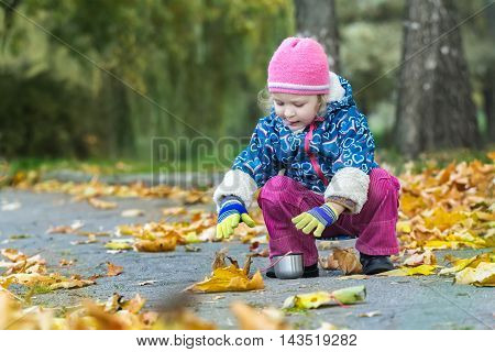 Two years old girl is stretching her hand to metal thermos flask cup hunkering at autumn foliage covering backdrop