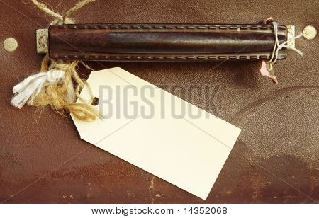 Blank luggage label tied to handle of vintage leather suitcase.