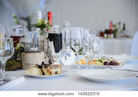 Served table with white tablecloth in the restaurant. Festive table with food and champagne in the Banquet hall. The celebration of luxury. Dinner party.