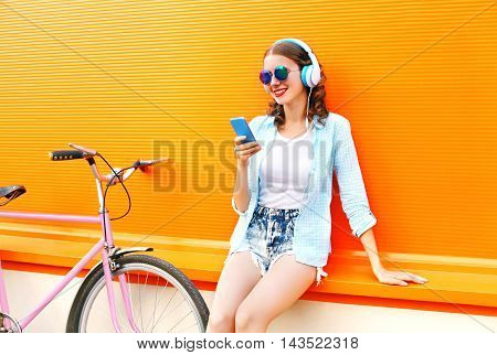 Fashion Pretty Young Woman Listens To Music Using Smartphone Near Urban Retro Bicycle Over Colorful