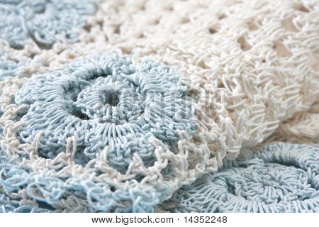 Crocheted doily in beige and pastel blue.  Close-up view of this lovely handcraft.