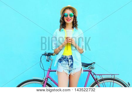Pretty Smiling Woman With Coffee Cup And Bicycle Over Colorful Blue Background