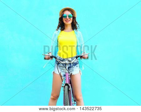 Pretty Smiling Young Woman Rides A Bicycle Over Colorful Blue Background
