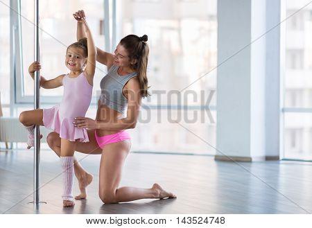 Adorable girl dancer and her teacher in the ballet studio