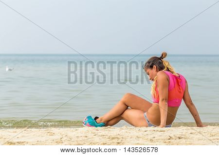 Beautiful Sporty Girl On The Beach Resting After Sport