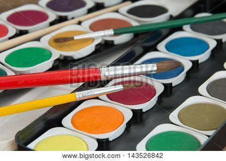 new unused palette of multicolor watercolor paints with paint brushes