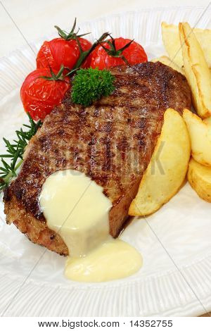 Grilled beef steak with potato wedges, cherry truss tomatoes, and bearnaise sauce.  Garnished with parsley and rosemary.