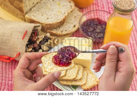 Crackers with jam served as breakfast - Woman hand holding a cracker with strawberry jam on it and in the background the breakfast table with bread, butter, orange juice and mixed nuts.