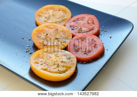 fresh tomato slices with spices and herbs on a black plate