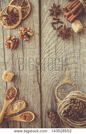 Selection of christmas spices on rustic wood background, top view