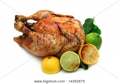 Roast chicken dinner - a plump, organic chicken with lemons and limes, ready for serving.