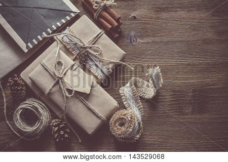Presents in rustic wrap, wood background, copy space, top view, toned