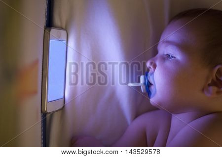 12 month old baby watching a lullaby cartoons with mobile phone on the crib