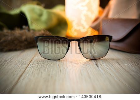 mirror sunglasses lying on the wooden desk with leather box , style isolated subject photo,