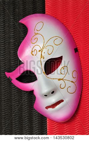 A masquerade mask isolated on a red and black background