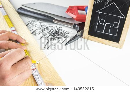 Man's hands measuring a wooden board having his tools in the background and a funny sketch of a house on a blackboard. Concept about building your dream house.