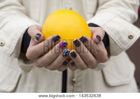 At the hands of the girl with the fashionable manicure fresh, bright orange lies