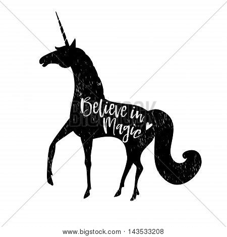 Believe in magic. Calligraphic text with hand drawn black silhouette of unicorn. Vector illustration background.