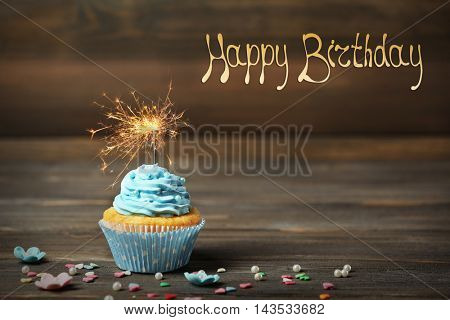 Birthday cupcake with sparkler on wooden background