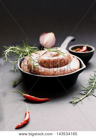 raw beef sausages on a cast-iron pan with rosemary and spices on a wooden table South African boerewors