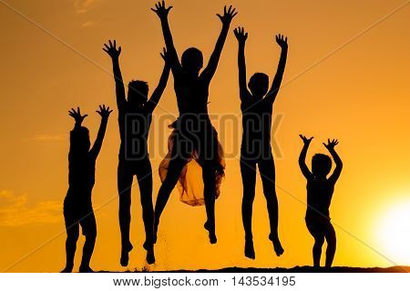 silhouette of five jumping kids against sunset