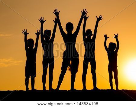 silhouette of group of children against sunset