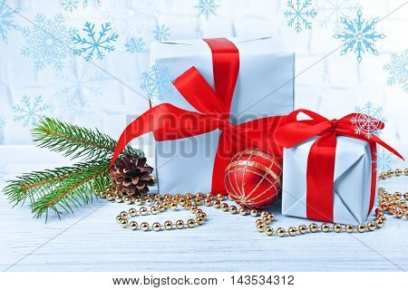 Gift boxes with Christmas tree branch and decor on brick wall background. Snow effect