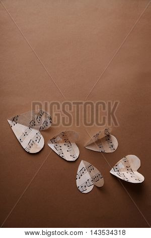 Paper hearts with music notes on brown background