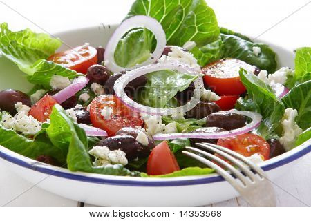 Greek salad in old enamel bowl, on wooden table.