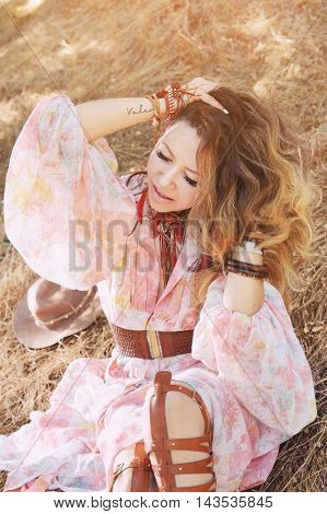 Beautiful happy smiling woman portrait sitting on a hay in autumn forest, boho, indie style